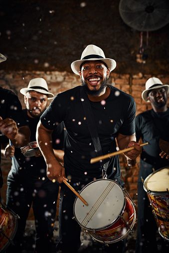 Portrait of a group of musical performers playing drums together