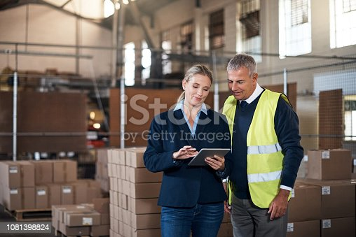 Shot of two factory managers working together in a warehouse
