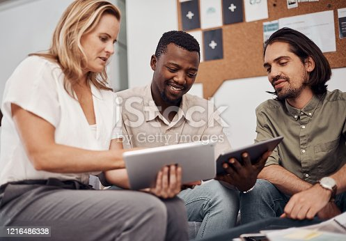 Shot of a group of businesspeople working together on a digital tablet in an office