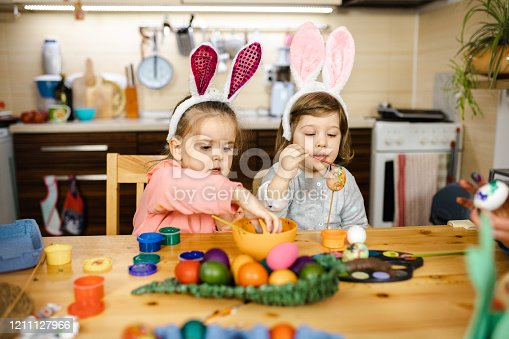 Lovely female siblings wearing bunny ears costume  while decorating easter eggs with watercolor paints, having fun and enjoying time together