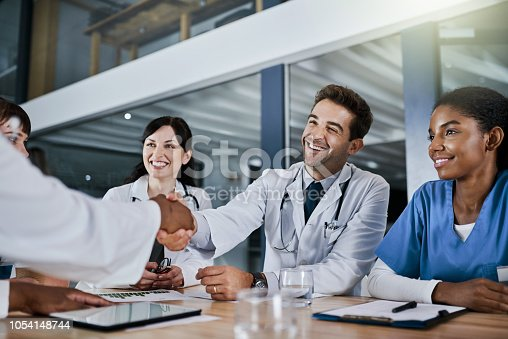 Shot of doctors shaking hands during a meeting in a hospital
