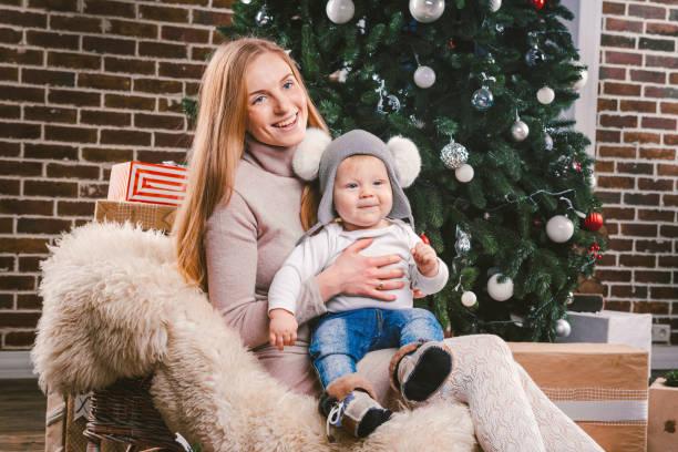 thema weihnachten urlaub winter neues jahr. eine junge mutter für stilvolle kaukasischen hält ihren sohn in die arme für 1 jahr in ein lustiges shirt sitzt auf einem schlitten und tragen fell unter dem baum eingerichtetes haus - baby born schlitten stock-fotos und bilder