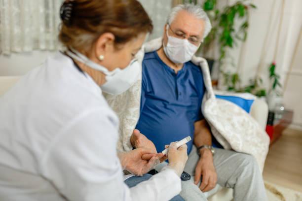 테마 당뇨병.그의 포도 당 의료 전문가의 가정에 가서 측정 된 남자. 그것은 혈액에 있는 포도당의 수준을 측정하기 위한 계기의 기술을 이용합니다 - diabetes 뉴스 사진 이미지