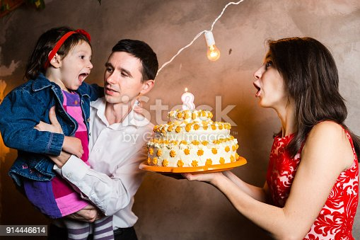 895137896 istock photo Theme family holiday childrens birthday and blowing out candles on large cake. young family of three people standing and holding 5 year old daughter in yard against gray wall and garland yellow bulbs 914446614