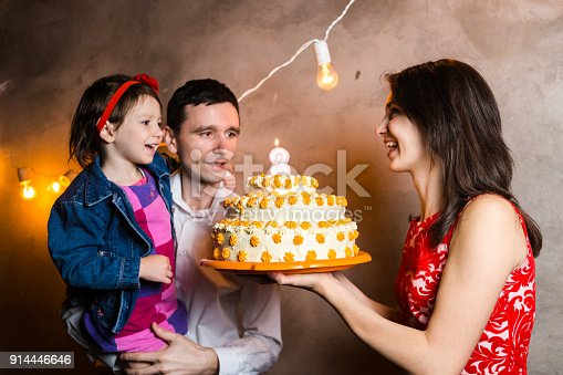 895137896 istock photo Theme family holiday childrens birthday and blowing out candles on large cake. young family of three people standing and holding 5 year old daughter in yard against gray wall and garland yellow bulbs 914446646