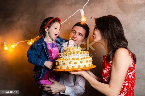 895137896 istock photo Theme family holiday childrens birthday and blowing out candles on large cake. young family of three people standing and holding 5 year old daughter in yard against gray wall and garland yellow bulbs 914446702