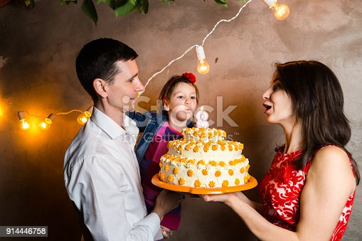 895137896 istock photo Theme family holiday childrens birthday and blowing out candles on large cake. young family of three people standing and holding 5 year old daughter in yard against gray wall and garland yellow bulbs 914446758
