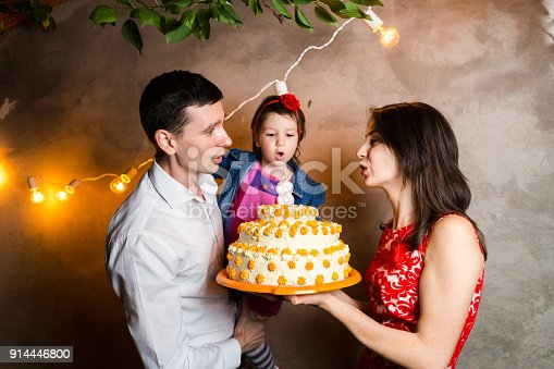895137896 istock photo Theme family holiday childrens birthday and blowing out candles on large cake. young family of three people standing and holding 5 year old daughter in yard against gray wall and garland yellow bulbs 914446800