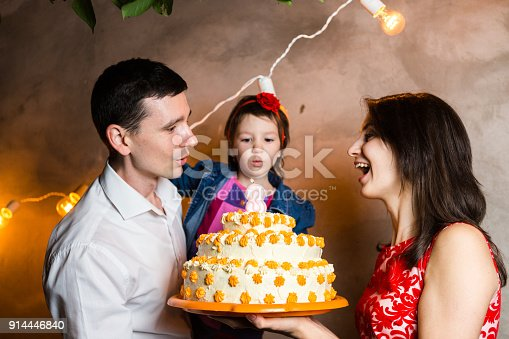 895137896 istock photo Theme family holiday childrens birthday and blowing out candles on large cake. young family of three people standing and holding 5 year old daughter in yard against gray wall and garland yellow bulbs 914446840