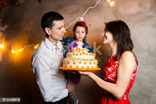 895137896 istock photo Theme family holiday childrens birthday and blowing out candles on large cake. young family of three people standing and holding 5 year old daughter in yard against gray wall and garland yellow bulbs 914446876