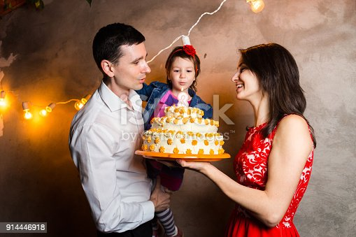 895137896 istock photo Theme family holiday childrens birthday and blowing out candles on large cake. young family of three people standing and holding 5 year old daughter in yard against gray wall and garland yellow bulbs 914446918