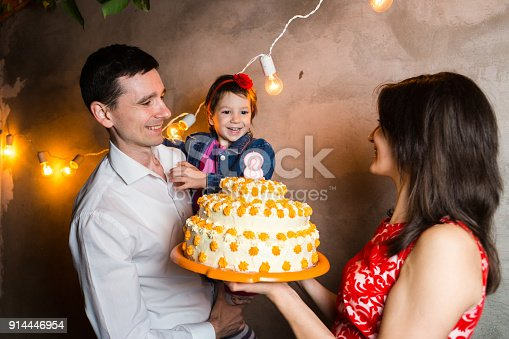 895137896 istock photo Theme family holiday childrens birthday and blowing out candles on large cake. young family of three people standing and holding 5 year old daughter in yard against gray wall and garland yellow bulbs 914446954