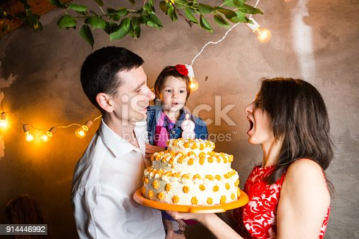 895137896 istock photo Theme family holiday childrens birthday and blowing out candles on large cake. young family of three people standing and holding 5 year old daughter in yard against gray wall and garland yellow bulbs 914446992