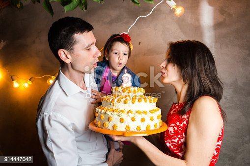 895137896 istock photo Theme family holiday childrens birthday and blowing out candles on large cake. young family of three people standing and holding 5 year old daughter in yard against gray wall and garland yellow bulbs 914447042