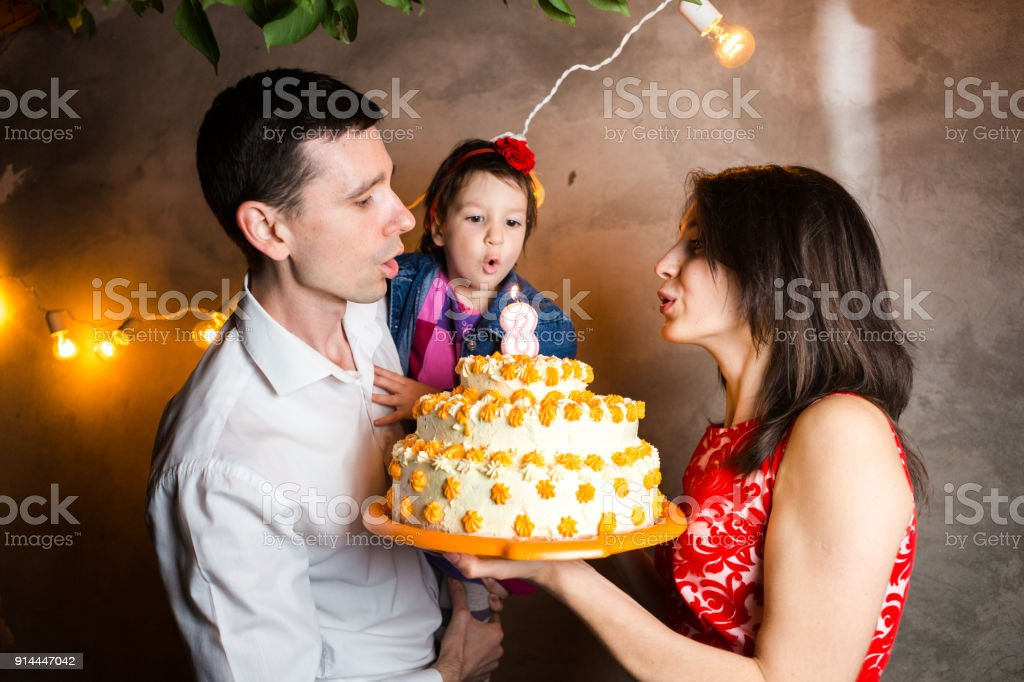 Theme family holiday childrens birthday and blowing out candles on large cake. young family of three people standing and holding 5 year old daughter in yard against gray wall and garland yellow bulbs stock photo