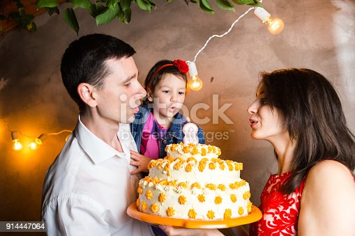895137896 istock photo Theme family holiday childrens birthday and blowing out candles on large cake. young family of three people standing and holding 5 year old daughter in yard against gray wall and garland yellow bulbs 914447064