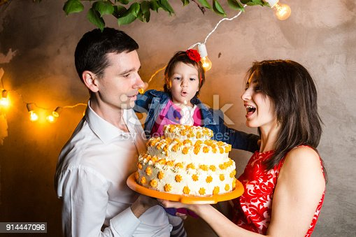 istock Theme family holiday childrens birthday and blowing out candles on large cake. young family of three people standing and holding 5 year old daughter in yard against gray wall and garland yellow bulbs 914447096