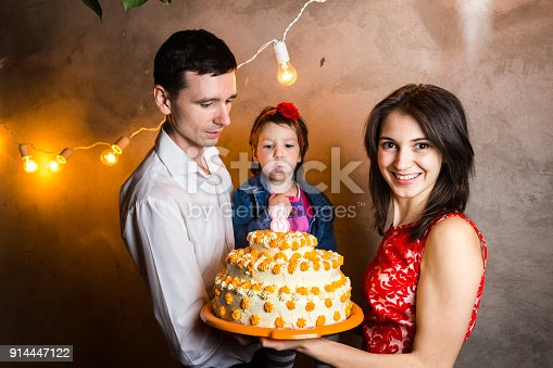 895137896 istock photo Theme family holiday childrens birthday and blowing out candles on large cake. young family of three people standing and holding 5 year old daughter in yard against gray wall and garland yellow bulbs 914447122