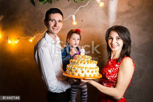 895137896 istock photo Theme family holiday childrens birthday and blowing out candles on large cake. young family of three people standing and holding 5 year old daughter in yard against gray wall and garland yellow bulbs 914447144