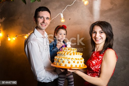 895137896 istock photo Theme family holiday childrens birthday and blowing out candles on large cake. young family of three people standing and holding 5 year old daughter in yard against gray wall and garland yellow bulbs 914447160