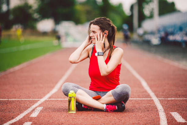 theme healthy lifestyle, sports music. young caucasian woman rests sitting treadmill running rubber stadium uses technodogy mobile phone hand insert earphones into ear include music training - runner rehab gym foto e immagini stock