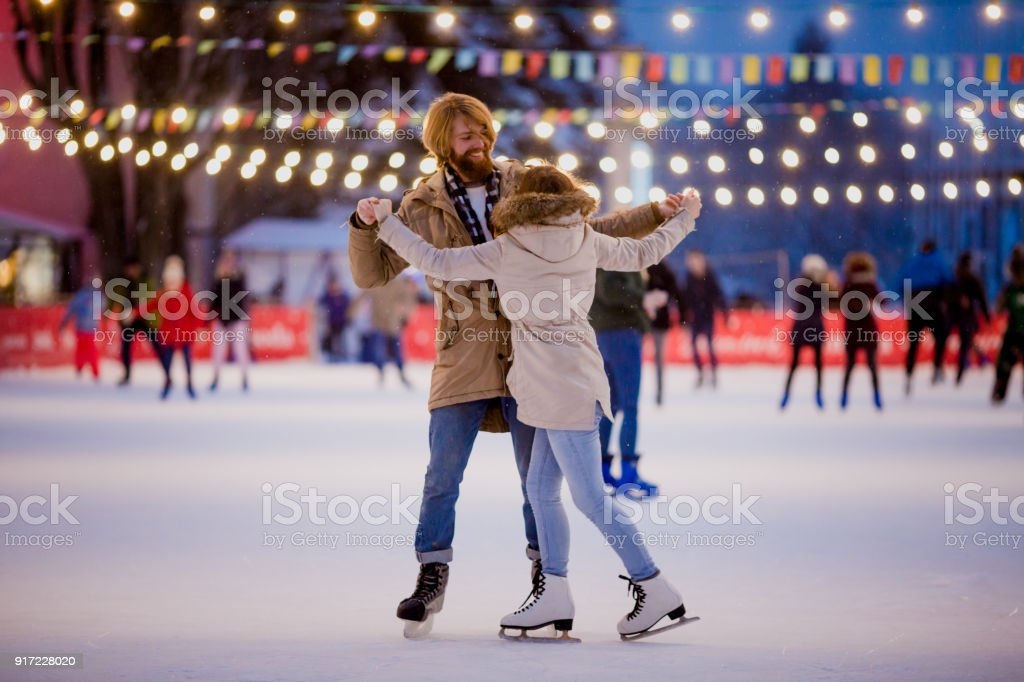 Theme ice skating rink and loving couple. meeting young, stylish...
