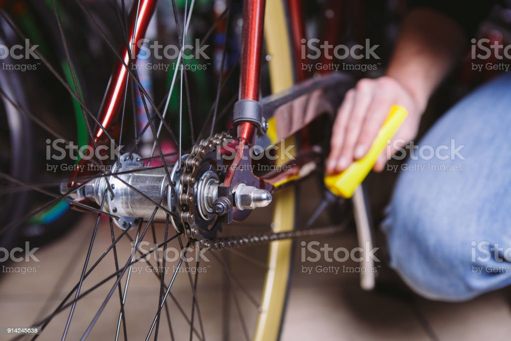 Theme repair bikes. Close-up of a Caucasian man's hand use a Chain Lubricant in a yellow lubricator for llubricator a bicycle chain on a red bicycle stock photo