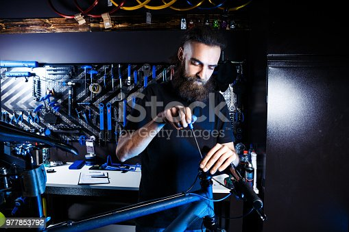 istock Theme sale and repair of bicycles. Young and stylish with a beard and long hair, a Caucasian man uses a tool to set up and repair a bike in a store. Business owner at work 977853792