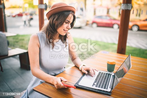 theme tourism and travel young student. beautiful young Caucasian girl in dress and hat sits in street cafe at wooden table using laptop technology and mobile phone. Search and book hotel and ticket.