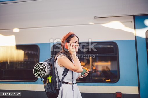 istock theme tourism and travel young student. beautiful young Caucasian girl in dress and hat standing at train station near train with backpack and cup coffee in hand. Uses smartphone phone technology 1170387125
