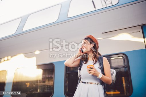 istock theme tourism and travel young student. beautiful young Caucasian girl in dress and hat standing at train station near train with backpack and cup coffee in hand. Uses smartphone phone technology 1170387154