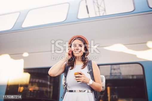 istock theme tourism and travel young student. beautiful young Caucasian girl in dress and hat standing at train station near train with backpack and cup coffee in hand. Uses smartphone phone technology 1170387214