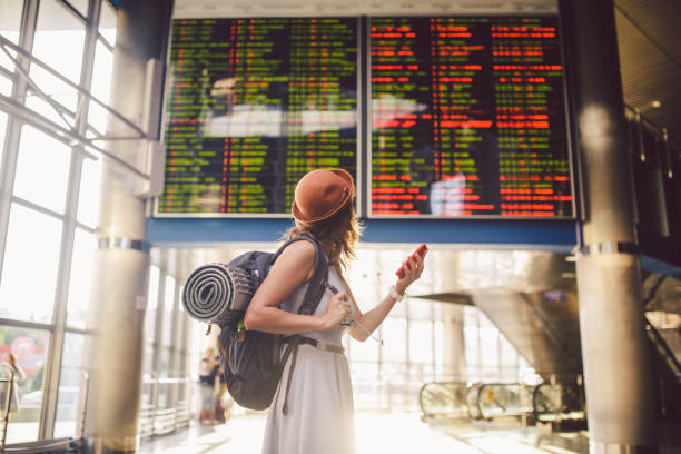 theme travel and tranosport. beautiful young caucasian woman in dress and backpack standing inside train station or terminal looking at a schedule holding a red phone, uses communication technology - aereo di linea foto e immagini stock