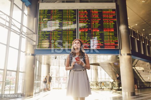 istock Theme travel and tranosport. Beautiful young caucasian woman in dress and backpack standing inside train station or terminal looking at a schedule holding a red phone, uses communication technology 1128332515