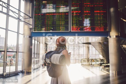 istock Theme travel and tranosport. Beautiful young caucasian woman in dress and backpack standing inside train station or terminal looking at a schedule holding a red phone, uses communication technology 1170387334