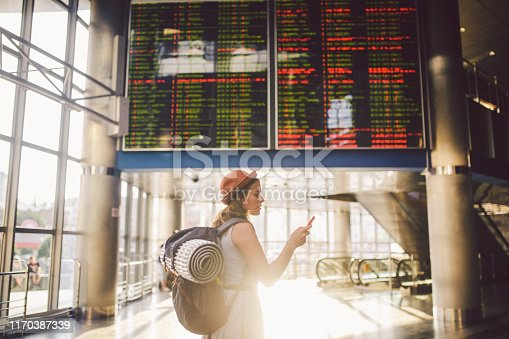 istock Theme travel and tranosport. Beautiful young caucasian woman in dress and backpack standing inside train station or terminal looking at a schedule holding a red phone, uses communication technology 1170387339