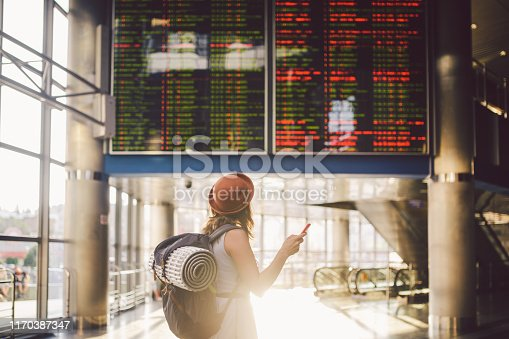 istock Theme travel and tranosport. Beautiful young caucasian woman in dress and backpack standing inside train station or terminal looking at a schedule holding a red phone, uses communication technology 1170387347