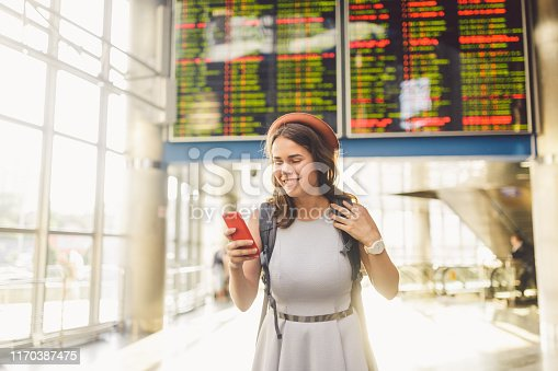 istock Theme travel and tranosport. Beautiful young caucasian woman in dress and backpack standing inside train station or terminal looking at a schedule holding a red phone, uses communication technology 1170387475