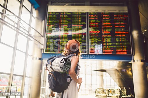 istock Theme travel public transport. young woman standing with back in dress and hat behind backpack and camping equipment for sleeping, insulating mat looks schedule on scoreboard airport station 1128332454