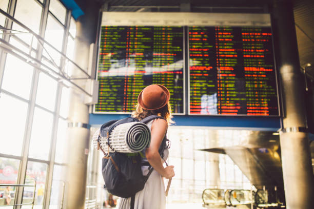 theme travel public transport. young woman standing with back in dress and hat behind backpack and camping equipment for sleeping, insulating mat looks schedule on scoreboard airport station - saccopelista foto e immagini stock