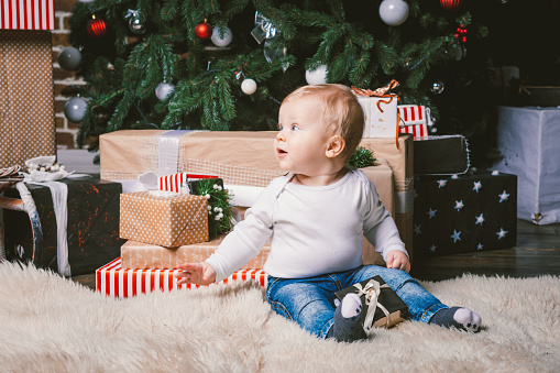 istock theme winter and Christmas holidays. Child boy Caucasian blond 1 year old sitting home floor near Christmas tree with New Year decor on shaggy carpet skin receives gifts, opens gift boxes in evening 1035188354