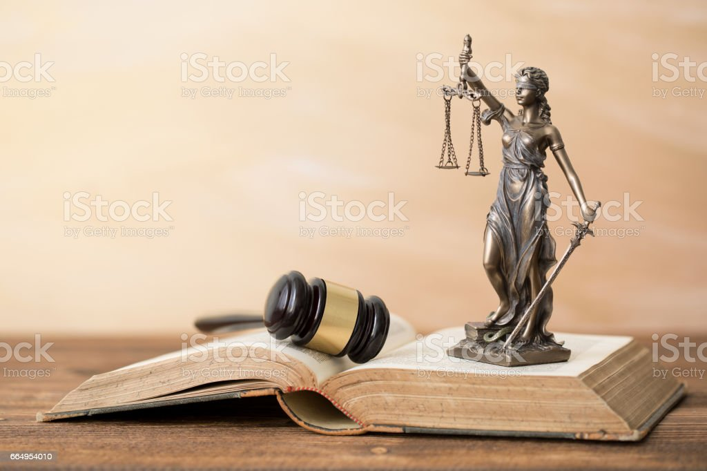 Themis statue on open book and gavel next to it stock photo