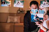 The young couple with a protective face mask shows a photo of them celebrating Valentine's Day before.