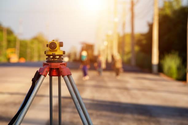 經緯儀挖掘機測量道路施工現場 - 陸地 個照片及圖片檔