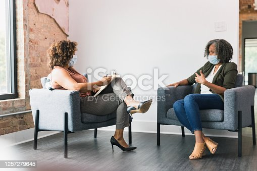 While wearing protective face coverings, a therapy patient and therapist discuss something. They are meeting during the COVID-19 pandemic.