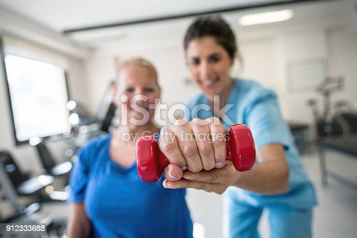 istock Therapist and patient holding a freeweight at the clinic both looking happy and smiling 912333688
