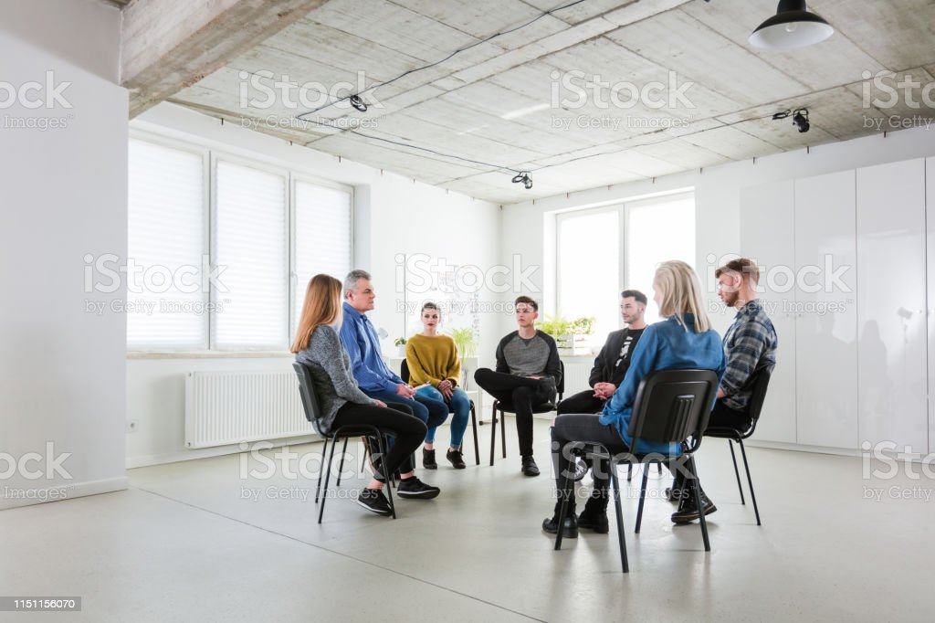 Therapist and students in therapy at lecture hall Full length of therapist and students sitting on chairs. Men and women are in group therapy at lecture hall. They are wearing casuals. 18-19 Years Stock Photo