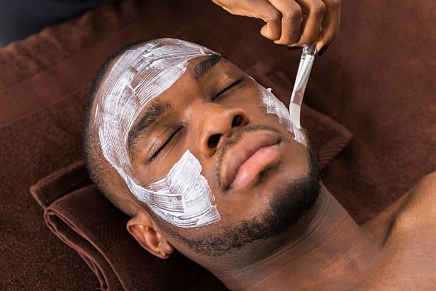 kosmetikerin anwenden gesichtsmaske auf mann - afrikanische masken stock-fotos und bilder