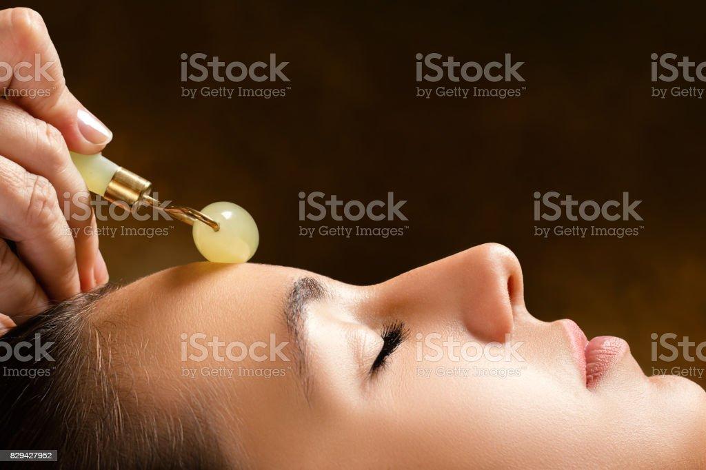 Therapist applying jade roller on female face. stock photo