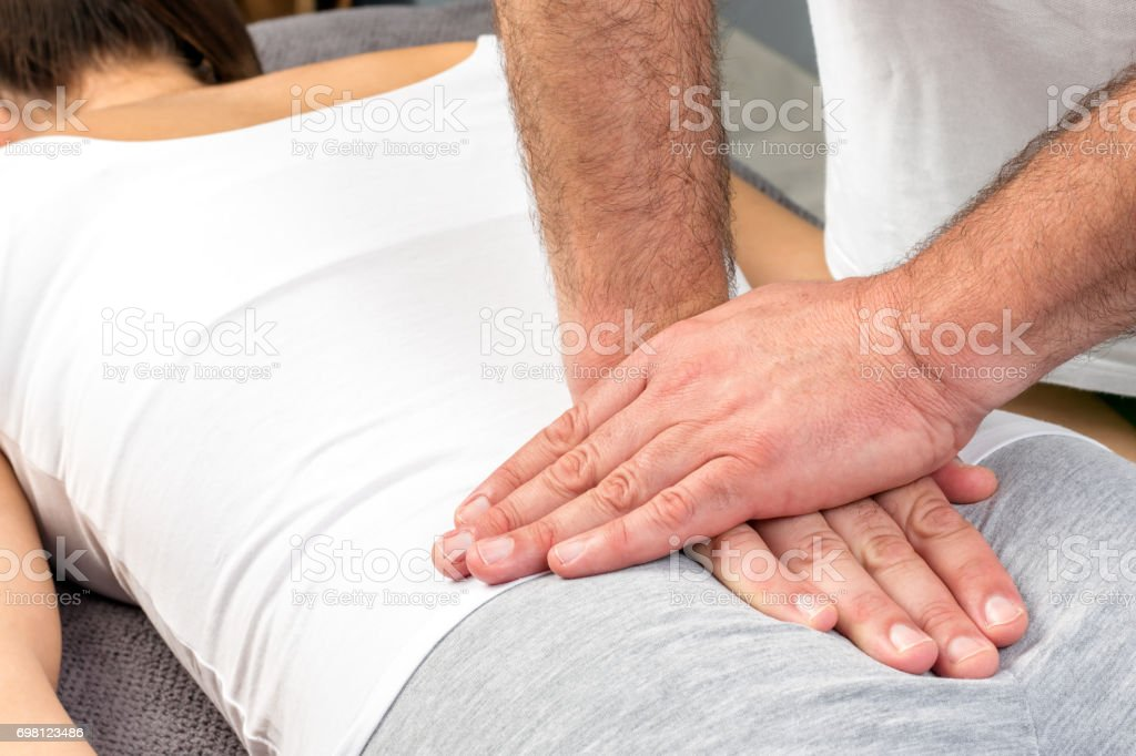 Therapist applying pressure on female tailbone. stock photo